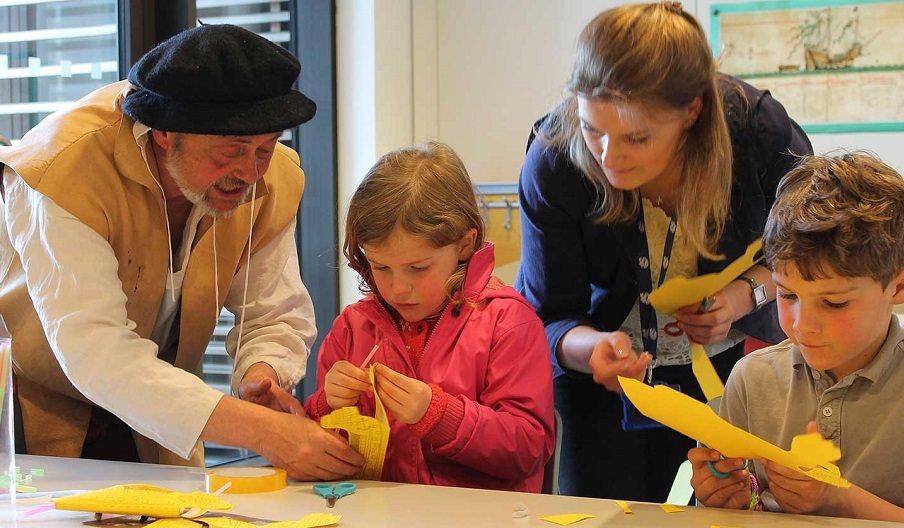 Tudor re-enactor helping children with craft activities