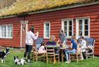 A family eating in front of one of the houses.