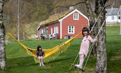 Two girls playing in front of one of the houses.