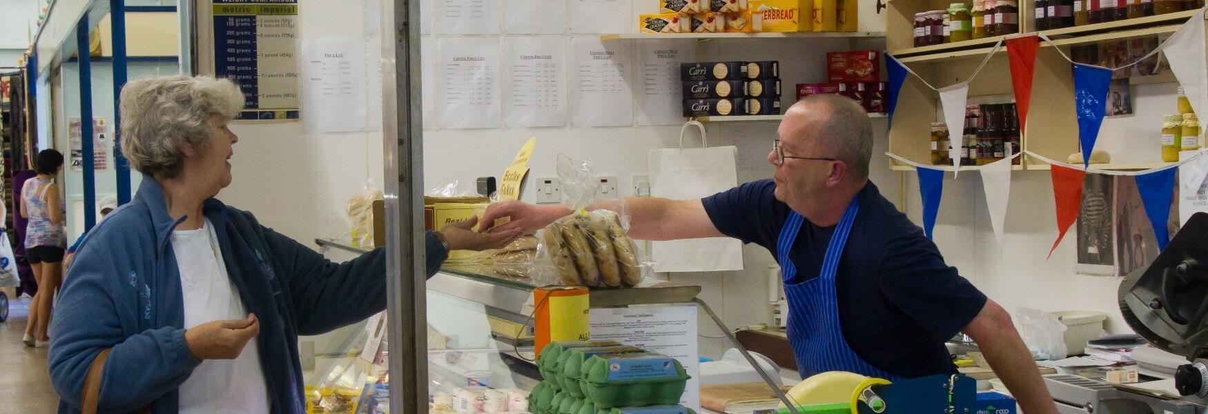 A market trader serving a customer.