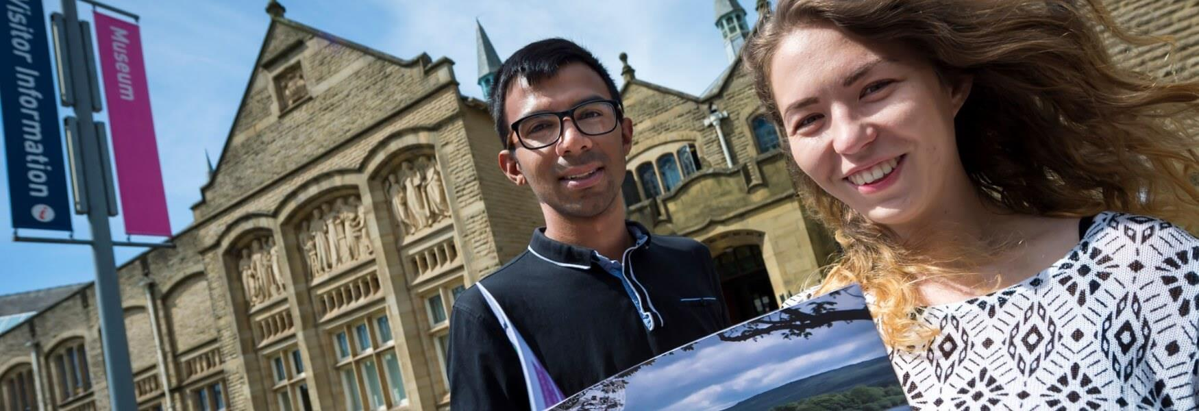 A smiling couple in front of Touchstones Rochdale.