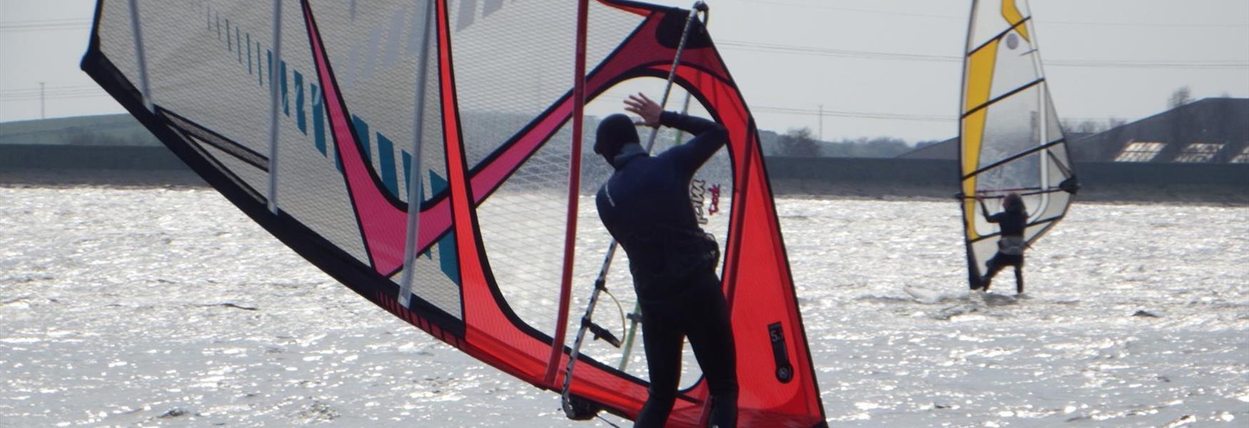 A lone windsurfer on Hollingworth Lake.