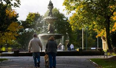 A family at a fountain in Queen's Park on a sunny day.