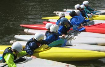 Row of People in Canoes
