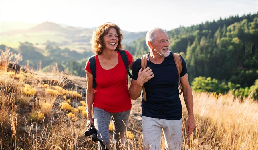 Couple walking across a field.