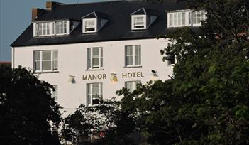 View of Manor Hotel bathed in evening sun light, as seen from the road