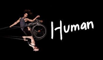 Black background. A photo of a woman and a man swinging in the air like a pendulum, looking powerful and graceful. They share a wheelchair which is he