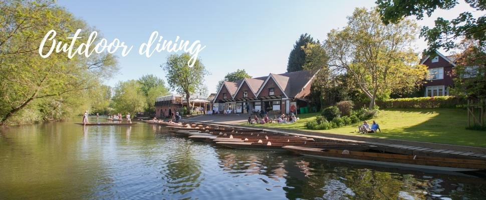 View of Cherwell Boathouse from the River with outdoor dining space and punts for hire
