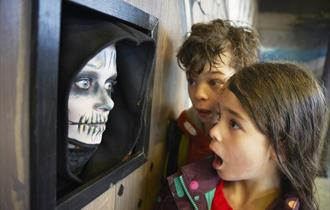 Two shocked looking children to the right look at wall on the left. Wall has a black frame with a human face painted like a skeleton.