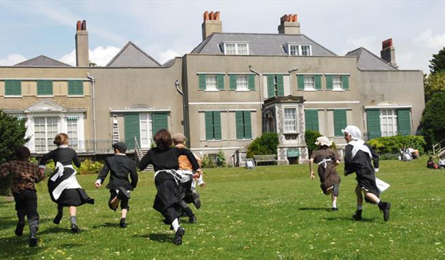 Children in historic dress running on lawn