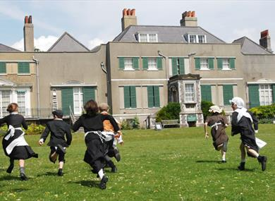 Children in historic dress running on lawn