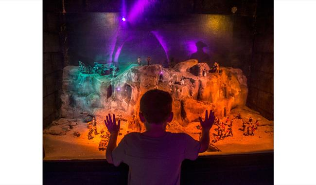 Child looking at a miniature model of smugglers using the caves