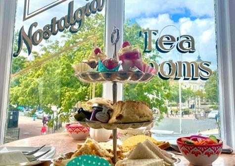 full cake stand in front of a window with Nostalgia Tea Rooms written on the window in cursive lettering