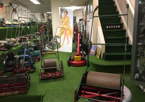interior of a museum with artificial grass and a display of vintage lawnmowers