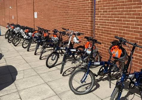 a row of bikes standing in front of a long brick wall