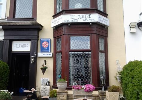 Front of a bed and breakfast called Le Maitre, with bay window and pink flowers in a windowbox