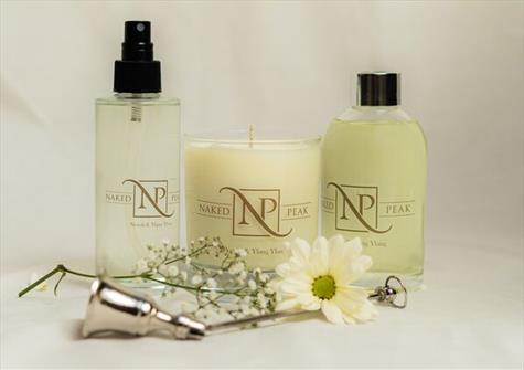 two clear bottles filled with pale yellow liquid, and candle. All branded with Naked Peak logo. Candle snuffer and gypsophilia in the foreground