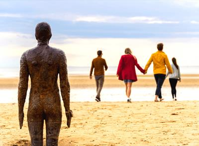 A weathered metal statue of a male is in standing in the sand looking out towards the sea. Walking towards the sea
