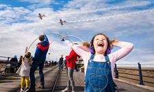 A young girl looks to the sky where two planes fly over