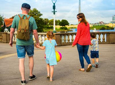 Family of man, woman and two children viewed from behind with a background of Southport Marine Lake