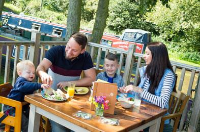 Family having lunch at Canalside Farm Cafe in the outdoor eating area.
