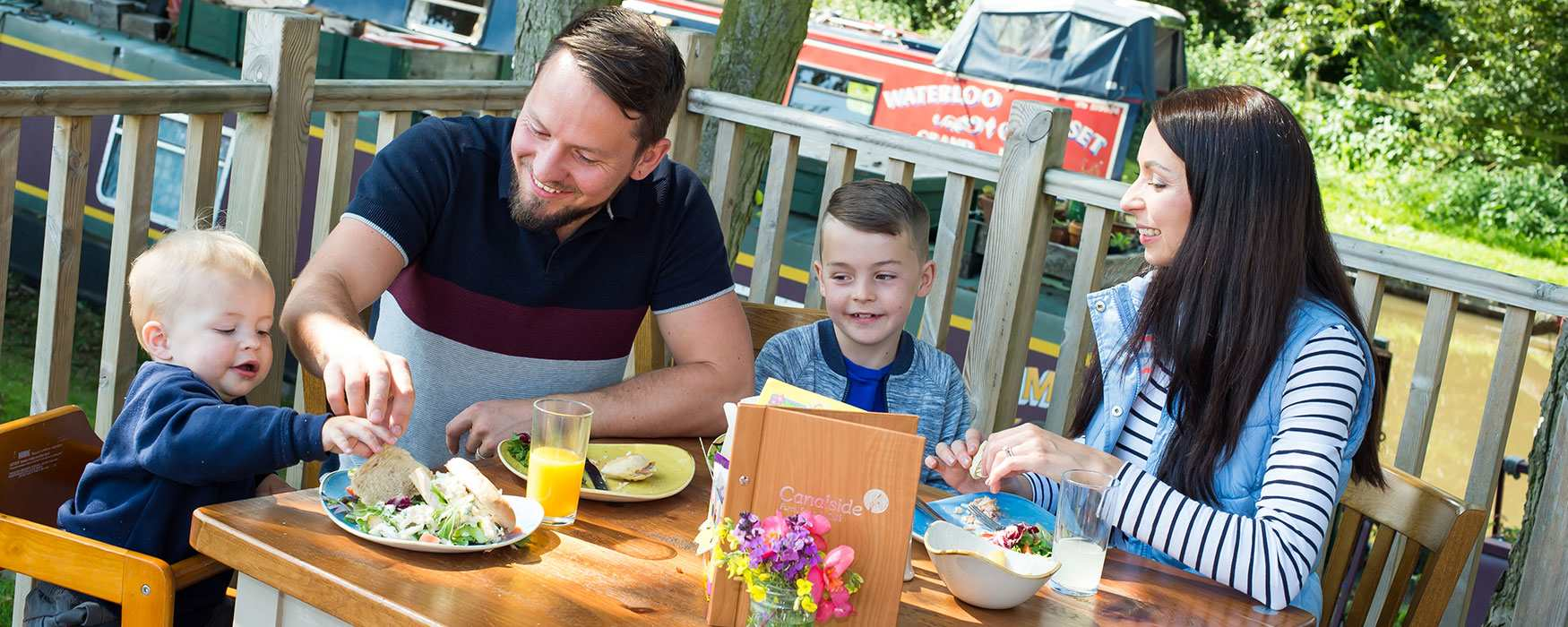 Family enjoying lunch on the outdoor terrace next to the canal at Canalside Cafe, Great Haywood