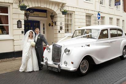 Classic Car with Bride and Groom outside the George Hotel.