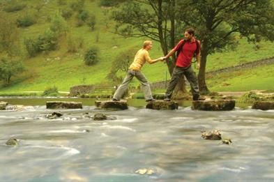Couple crossing the famous Stepping Stones across the River Dove, Dovedale, Peak District. Staffordshire / Derbyshire border. Image courtesy Tony Plea