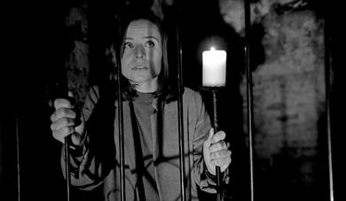 Girl standing behind bars with candle, The Lost Crypt Escape Room at Aspire Ryde, Isle of Wight, Things to Do