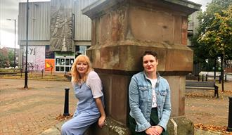 Two women sits on a memorial