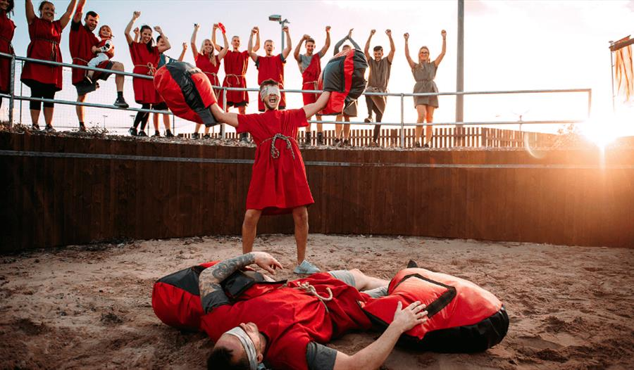 A group of people dressed in Roman attire standing around a battle arena cheering two people in the middle.