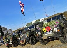 four military jeeps lined up in a row, one of them is flying a union jack flag.