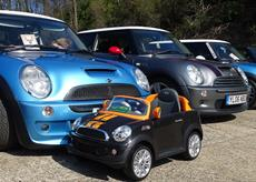 Four Mini brand cars lined up next to eatch other with a smaller Mini for children in front of them.