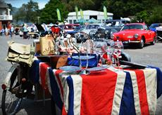 table with union jack table cloth, glasses and ornaments on the table, lots of old cars in the background