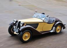 a old yellow and black classic/vintage car in motion along a race track