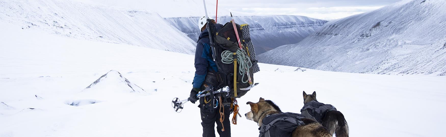 En person med fullpakket sekk som står på en isbre sammen med to hunder
