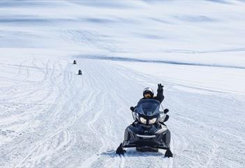 A person driving a snowmobile