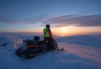 En guide på en snøscooter som nyter utsikten
