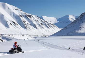 En rekke med snøscootere som kjører på tur