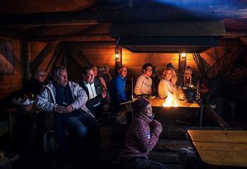 Gjester som følger med på et foredrag inne i hytta på Camp Barentz