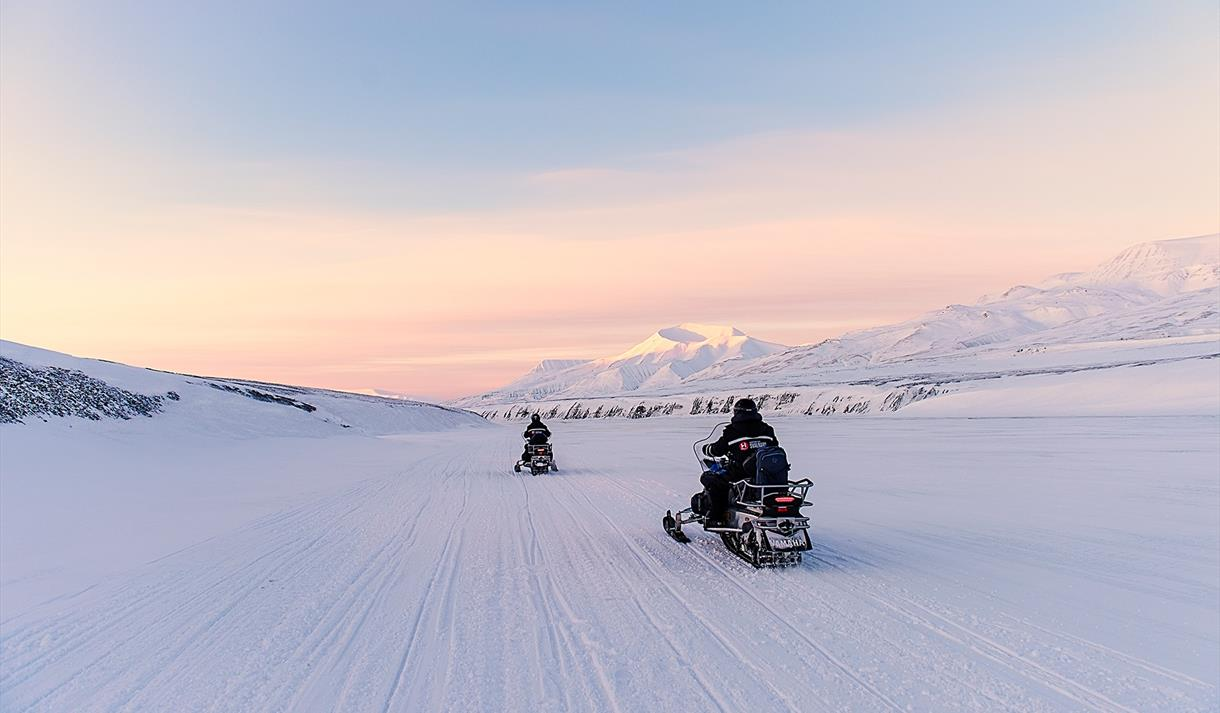 People driving snowmobiles