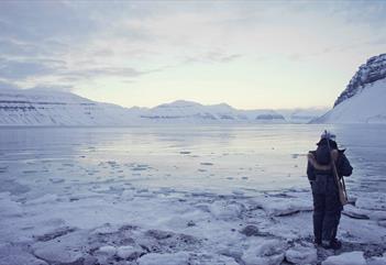 Guide stående ved isen med rifle