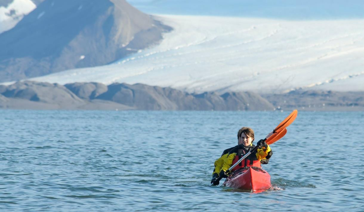 Two guests paddling in a double kayak on a fjord with a glacier behind them