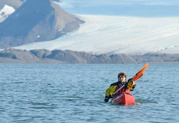 To gjester som padler i en dobbelkajakk på en fjord med en isbre i bakgrunnen