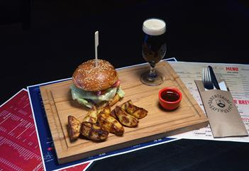 A burger meal on a wooden plate