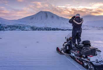 A guide standing on a snowmobile scouting out the terrain using binoculars