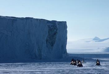 A tour group on snowmobiles with an ice wall in the background