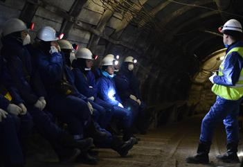 A group of guests sitting and listening to their guide inside of Barentsburg mine