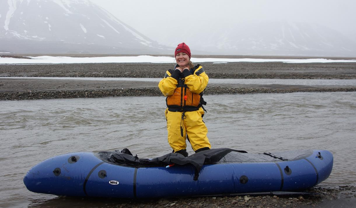 A guest in a wetsuit standing behind a packraft in a river