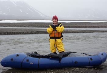En gjest i våtdrakt som står bak en packraft i en elv